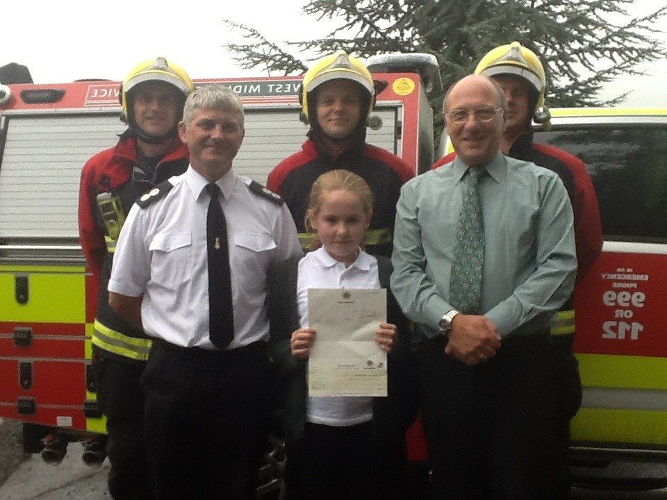 Draw winner Emma with Watch Commander Ade Lyden, Head Teacher Mr Graham Catt and some of the Crew from Red Watch Northfield