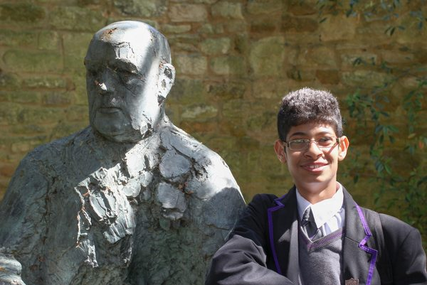 An ARK Kings student standing by a statue of Wadham College warden Bowra