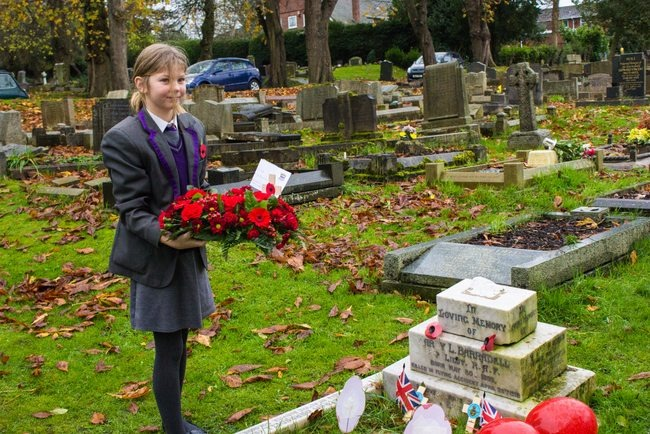 ARK Rose Primary pupil lays wreath on a war grave