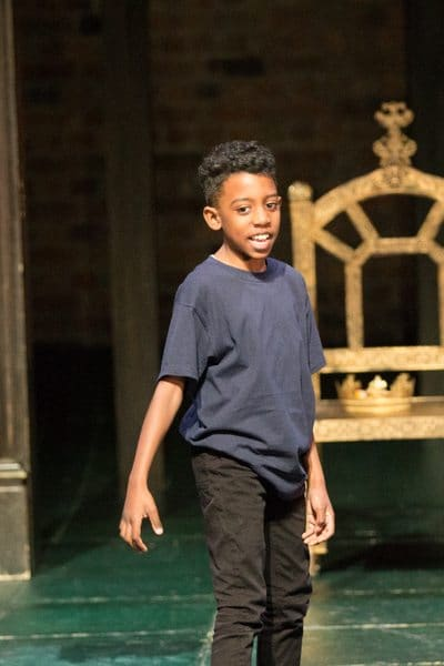 ARK Rose Primary Academy pupil standing tall as part of the RSC production of 'The Head that Wears a Crown'