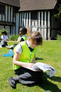 A pupil from Ark Rose Primary Academy sits on the grass in St Nicolas' Place and writes notes about her learning walk in Kings Norton