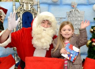 Santa greets a local youngster at his igloo grotto at Northfield Shopping Centre