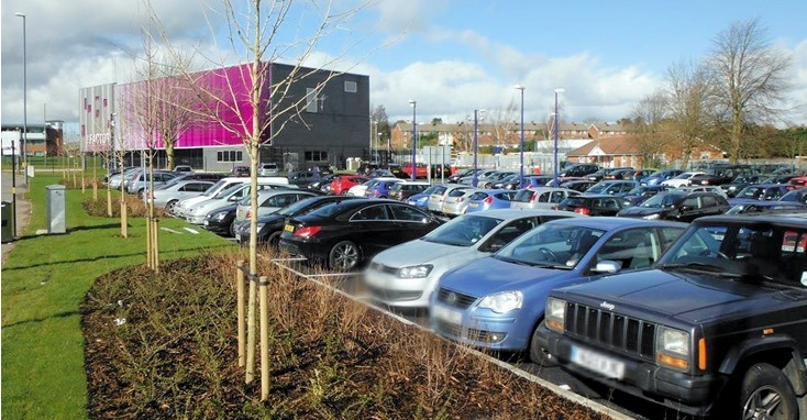 Cars in the land level Park and Ride car park adjacent to Longbridge Station. The Factory Youth Centre building in the background