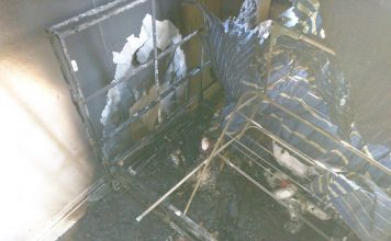 Severe fire damage including burnt bedding, mattress and wall