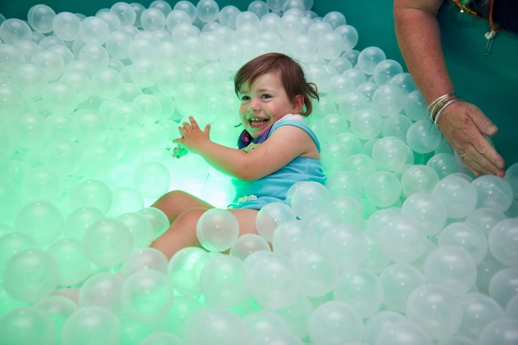 Libby plays in a ball pit clear balls lit from underneath by colourful light at Sense TouchBase Pears