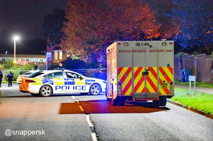 Police car and tape blocking Holly Hill Road with a Police Incident Support Van close by. Following a shooting in Mowbray Close, Frankley
