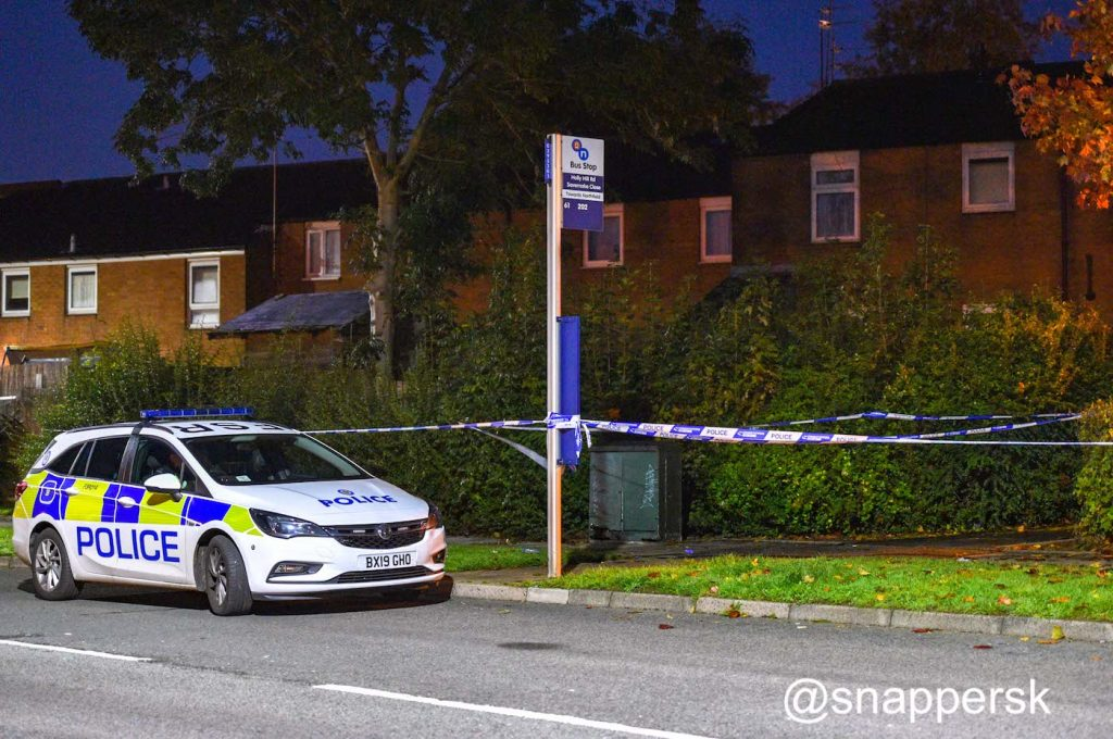A police car by a bus stop with police tape on Holly Hill Road next to the footpath into Mowbray Close