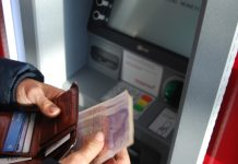 Man holding cash at ATM cash machine